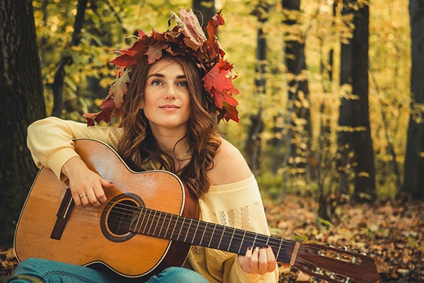 Girl playing guitar in the forest